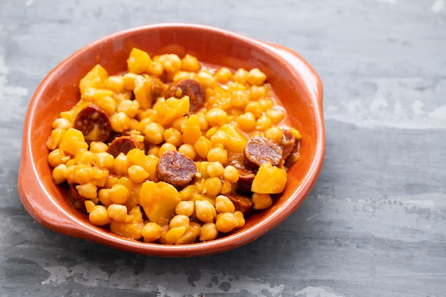 セラミック皿にジャガイモとスモークソーセージを添えたひよこ豆
