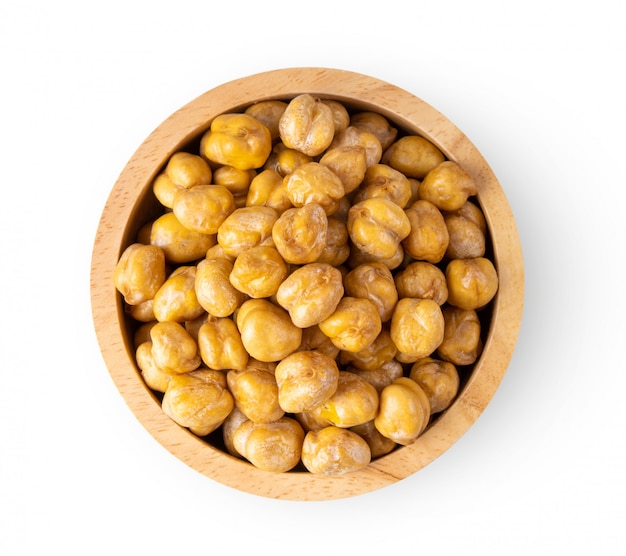 Chickpea in wood bowl on white wall.