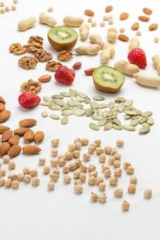 Нут, миндаль, грецкие орехи и фрукты для energy healthy breakfast. белая поверхность. вид сверху.