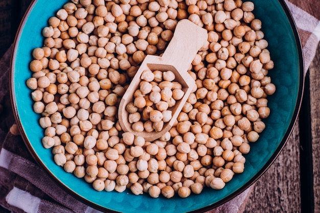 Chickpeas in bowl on tablecloth with wooden spoon on wooden table. healthy vegan food