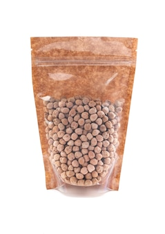 Chickpeas in a brown paper bag. doy-pack with a plastic window for bulk products. close-up. white background. isolated.
