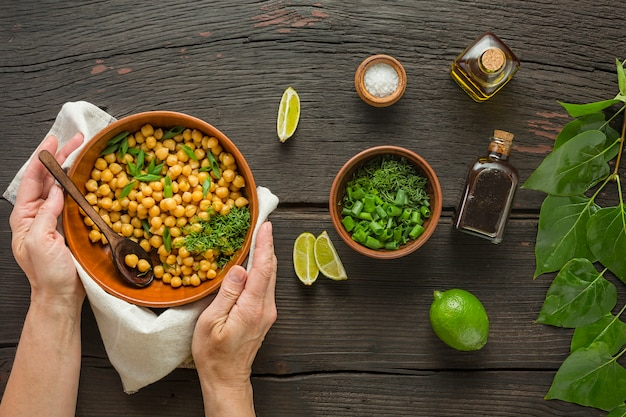 Chickpeas garnish. woman serves boiled chickpeas in a bowl on a dining table. vegetarian food
