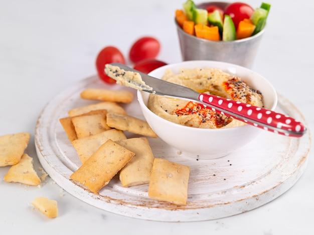Нут хумус и свежие овощи закуска блюдо с крекерами на светлом фоне. здоровые закуски, диета, концепция питания.