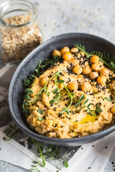 Chickpeas hummus in the black bowl decorated with sesame seeds and chickpeas greens.