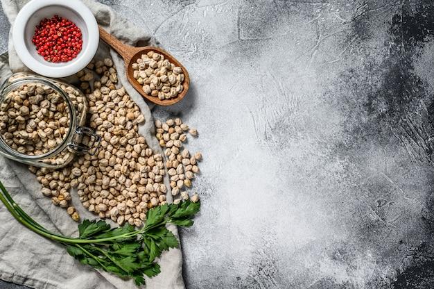 パセリとピンクのコショウでガラスの瓶にひよこ豆。健康的なベジタリアン料理。灰色の背景。上面図。テキストのためのスペース。