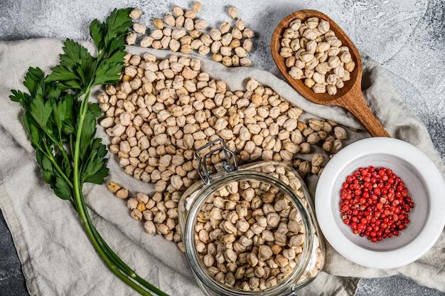 パセリとピンクペッパーのガラス瓶にひよこ豆。健康的なベジタリアン料理。灰色の背景。上面図
