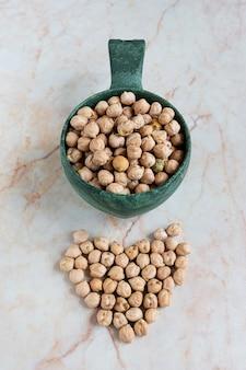 大理石の背景にスクープのひよこ豆