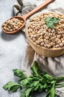 木のスプーンでひよこ豆。健康的なベジタリアン料理。灰色の背景。上面図