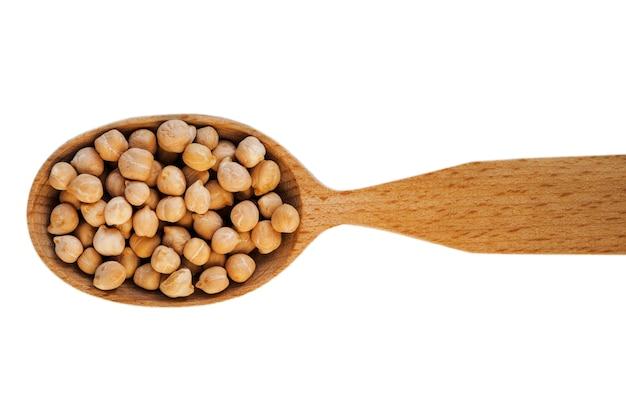 白い背景の上面図に分離された木のスプーンでひよこ豆