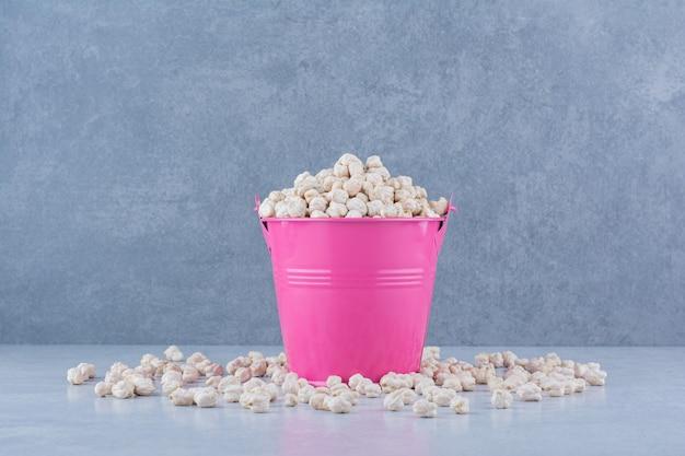 ひよこ豆は大理石の背景に小さな紫色のバケツの中と周りに散らばっています。