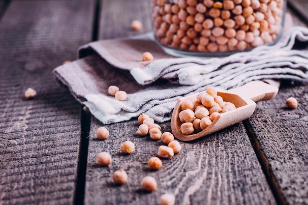 木製のテーブルに木のスプーンでガラスの瓶にひよこ豆。健康的なビーガンフード、トップビュー