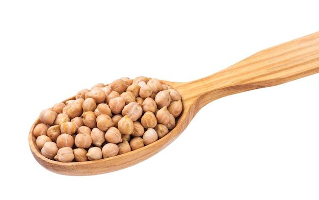 木のスプーンで白で隔離のひよこ豆。