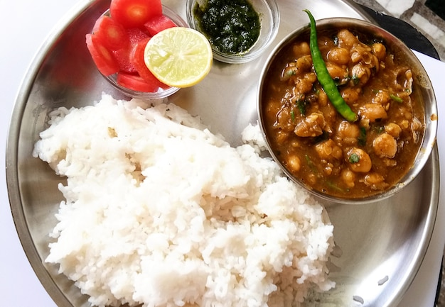 Chickpeas masala with rice - chole masala curry and cooked plain white rice, chole chawal or chole rice, traditional north indian lunch, dinner menu
