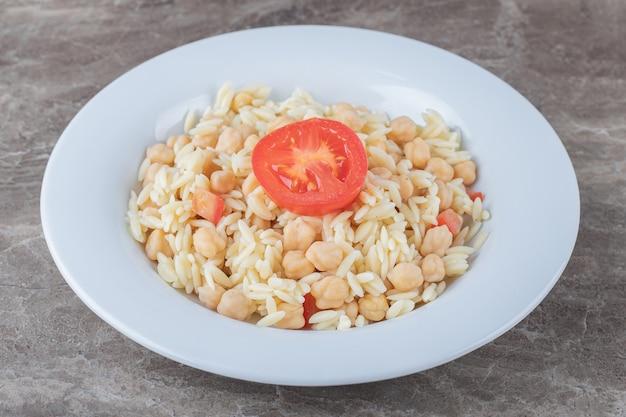Ceci e pasta con pomodoro a fette sul piatto, sul piano di marmo.