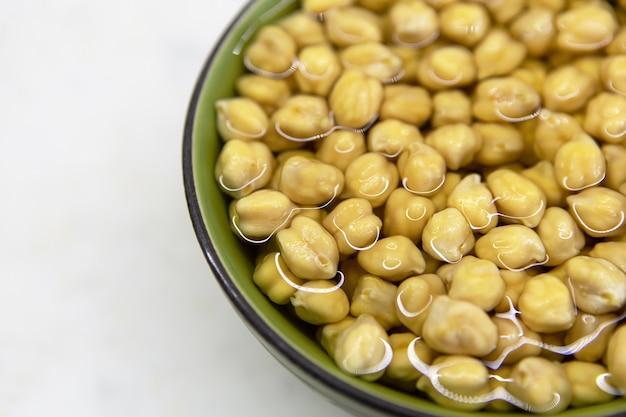 ひよこ豆を水に浸し、ボウルに入れ、大理石のテーブルの上に置きます。健康的な食事、ビーガニズム、菜食主義、肉と卵の交換の概念。フムスや他のマメ科植物の料理を作る前にひよこ豆を準備します。