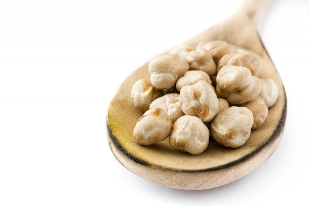 Chickpeas uncooked on wooden spoon isolated  copy space