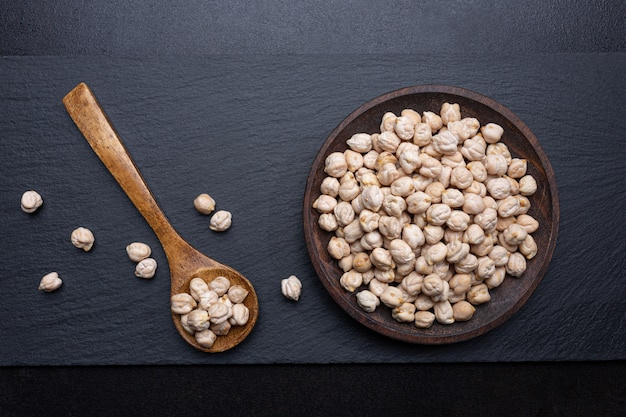 Chickpeas on  wooden plate and wooden spoon