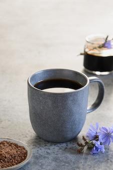 Напиток цикорий как заменитель кофе в серой чашке и свежих цветах. вертикальный формат.