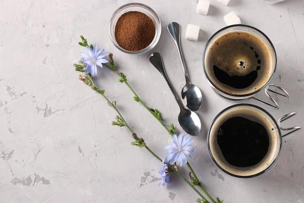 灰色の背景に濃縮物と花が付いた、2つのガラスカップに入ったチコリ飲料。健康的なハーブ飲料、コーヒー代用品、テキスト用スペース、上面図