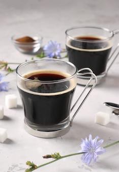 Напиток цикорий в двух стеклянных чашках, с концентратом и цветами на сером