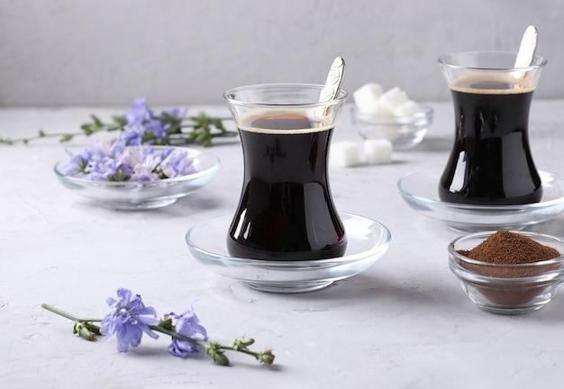 ライトグレーの背景に濃縮物と花が付いた、2つのガラスカップに入ったチコリ飲料。健康的なハーブ飲料、コーヒー代用品
