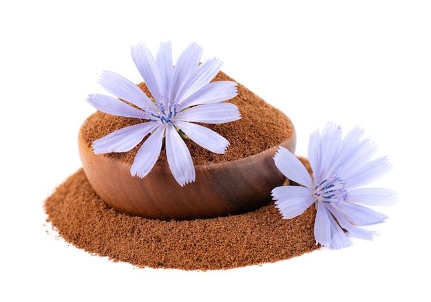 チコリの粉と木製のボウルに花、白い背景で隔離。 cichoriumintybus。