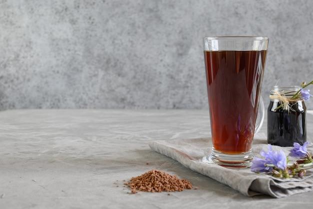 Корень цикория кофе в стаканах и живые цветы. польза для здоровья. мгновенно и сконцентрироваться. закрыть вверх