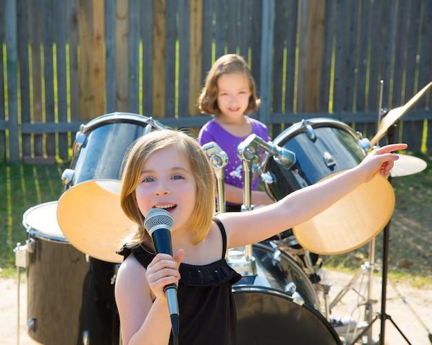 裏庭でライブバンドを演奏歌っている子供歌手の女の子