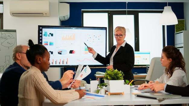 エコノミストのチームのために会議のプレゼンテーションを開催するチーフアナリスト。成長分析、チャート、統計、データ、ブロードルームで働く多様な人々を備えたデジタルインタラクティブホワイトボードを示すマネージャー