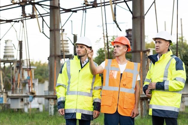 Главный инженер и специалисты изучают отчет об инвестициях на строительство электростанции.