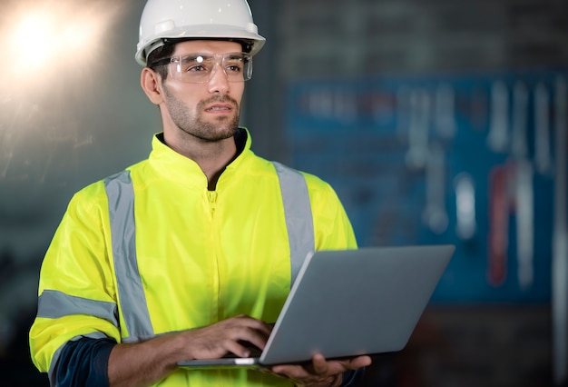 Chief engineer in the hard hat walks through light modern factory while holding laptop.
