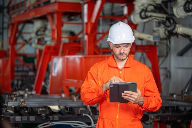 ハード帽子のチーフエンジニアは、ラップトップを握っている間、ライトモダンな工場を通り抜けます。現代の産業環境で成功したハンサムな男。