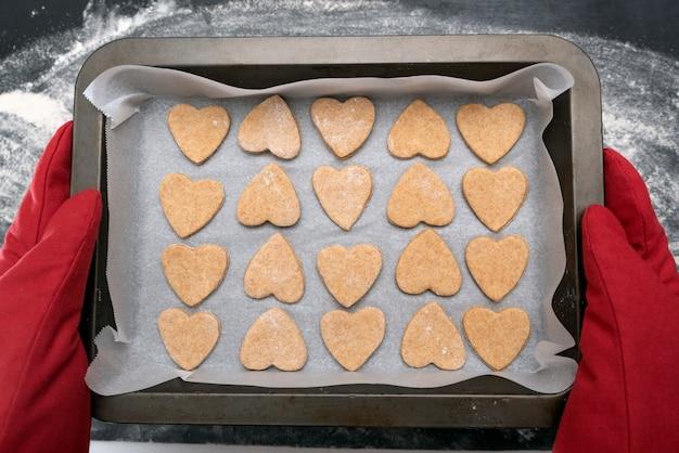 焼きたてのハート型のクッキーを持ったオーブンミットのチーフ。上面図。