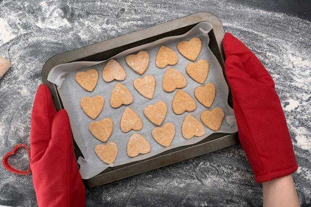 焼きたてのハート型のクッキーを持ったオーブンミットのチーフ。