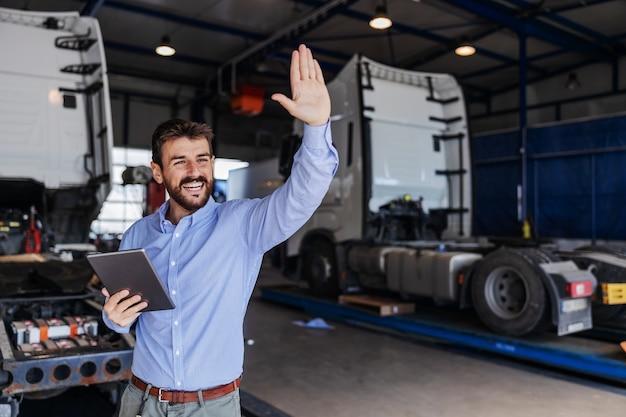 Начальник стоит в гараже транспортной фирмы, держит планшет и машет рукой.