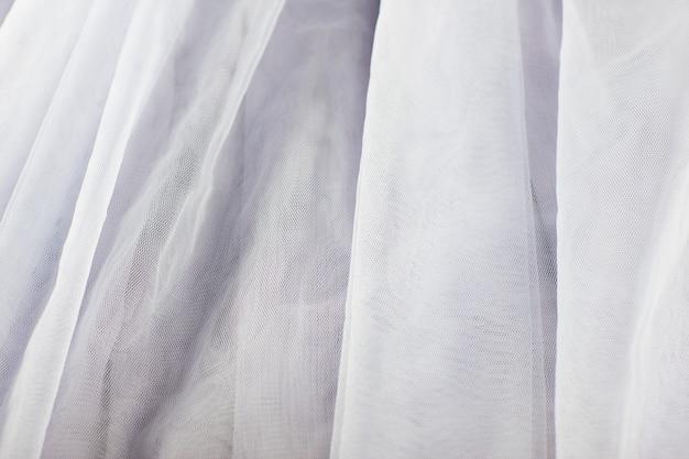 シフォンチュール生地の織り目加工の背景。プリーツスカート生地の風合い。クローズアッププリーツ生地のテクスチャパターン