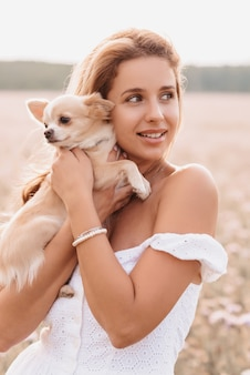 Chihuahua dog in the hands of a girl in a field in the summer in nature