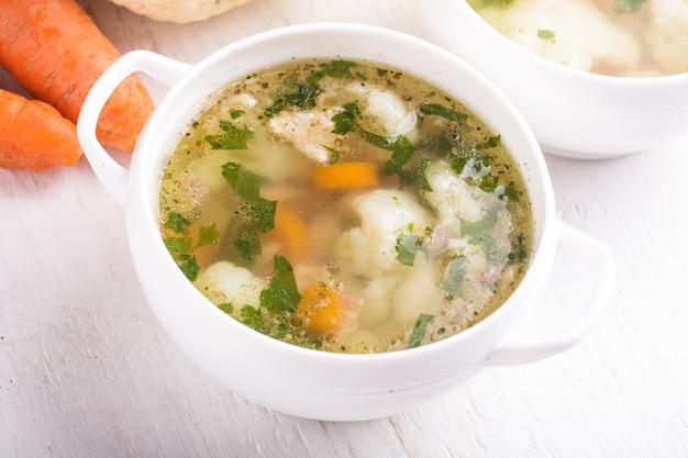 白いカップにチケンカリフラワーとにんじんのスープ