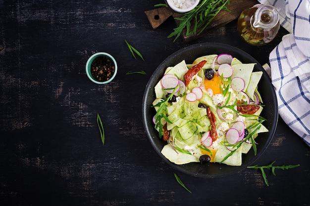 Чилакилес (в мексиканской кулинарии) блюдо из жареных полосок тортильи с яйцом и сыром. мексиканская еда. мексиканский завтрак. вид сверху, плоская планировка, копия пространства