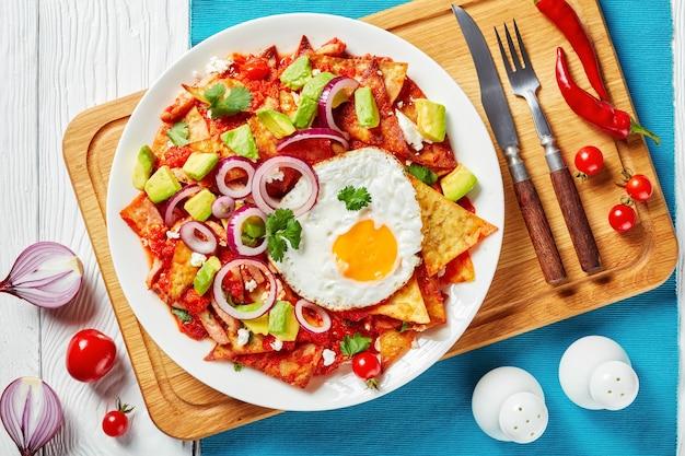 도마, 멕시코 요리, 위에서보기, 근접 촬영에 흰색 접시에 튀긴 계란, 햄, 부서진 panela 치즈, 아보카도, 토마토 살사와 chilaquiles