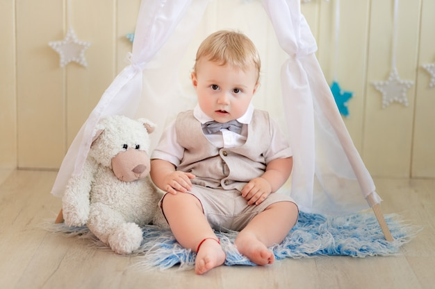 Ребенок 1 год мальчик в костюме сидит с медведем в вигваме