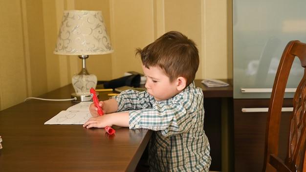 子供2-3は、テーブルに座って絵を描きます。