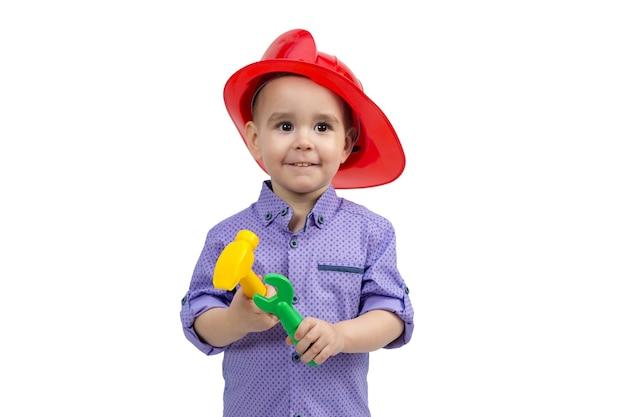 手に建設ツールを持ったヘルメットをかぶった3歳の子供。