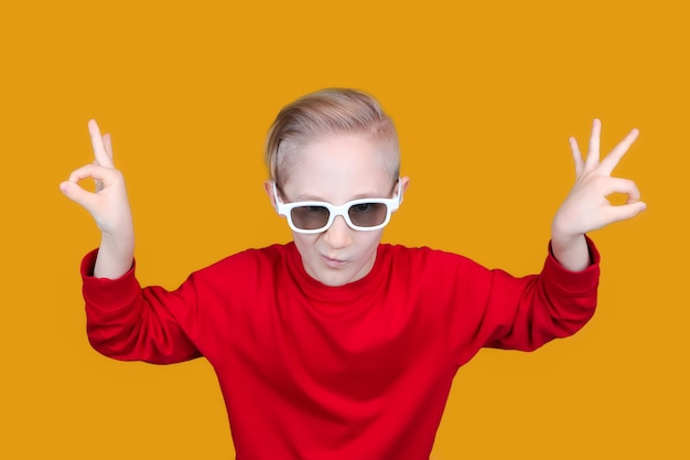 Child in 3d movie glasses shows hand gesture ok