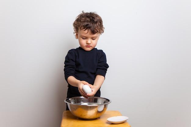 Ребенок, мальчик в черной футболке моет руки с мылом на белой студии.