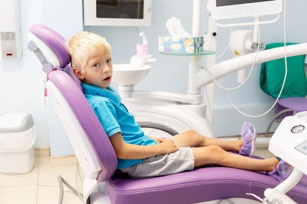 Пятилетний мальчик в синей футболке сидит в сиреневом кресле в стоматологическом кабинете.