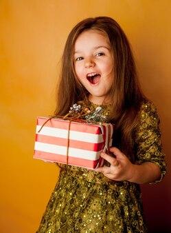 子供-彼女の手にクリスマスプレゼントを持っているドレスを着た女の子