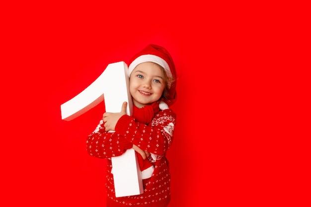 Ребенок маленькая девочка держит номер один в шляпе санта-клауса на красном фоне, место для текста