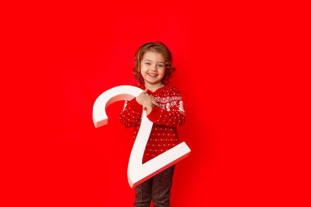 Ребенок маленькая девочка держит номер два в зимней одежде на красном фоне, место для текста