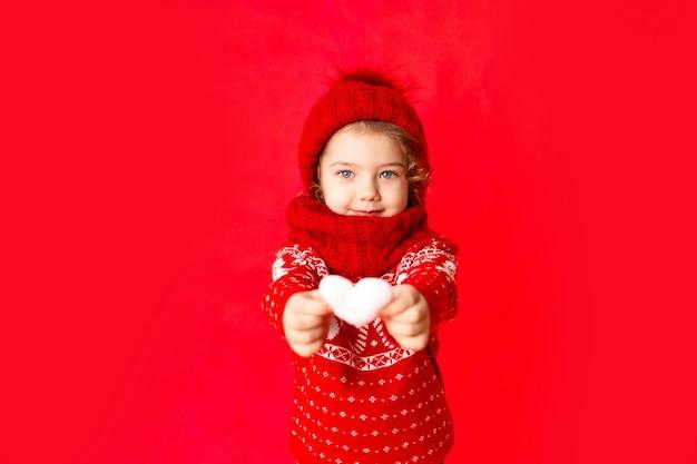 Ребенок маленькая девочка в зимней одежде держит сердце на красном фоне. концепция нового года или дня святого валентина, место для текста